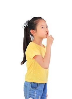 Portrait of asian kid girl shows shh sign
