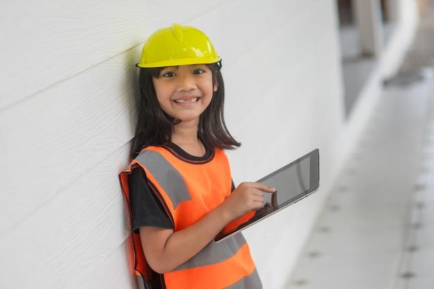 반사 셔츠와 태블릿에 하드 모자 안전 쓰기 기록을 입고 초상화 아시아 꼬마 소녀. 학습 및 개발 향상, 작은 건축가.