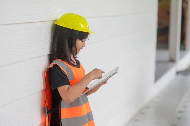 태블릿에 반사 셔츠와 안전모 안전 쓰기 기록을 쓴 초상화 아시아 꼬마 소녀