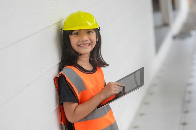 Portrait asian kid girl wearing a reflective shirt and hard hat safety writing record on tablet. to learning and enhance development, little architect.