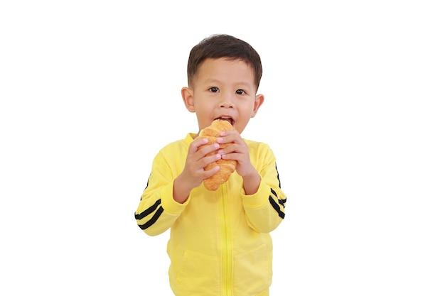 Портрет азиатского маленького мальчика, едящего круассан