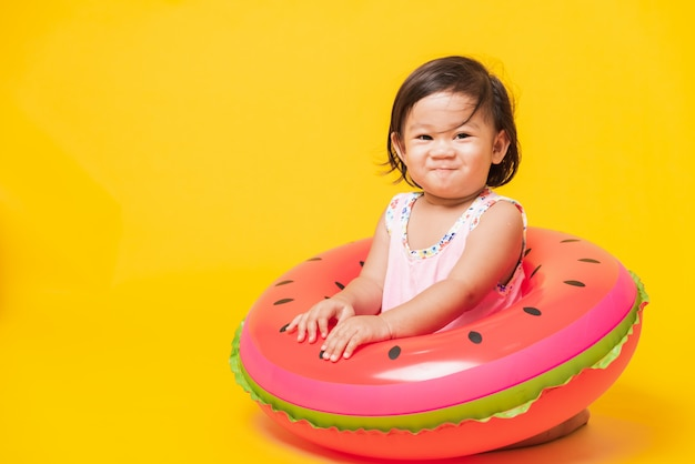 Portrait of asian little baby girl wear swimsuit sitting in watermelon inflatable ring