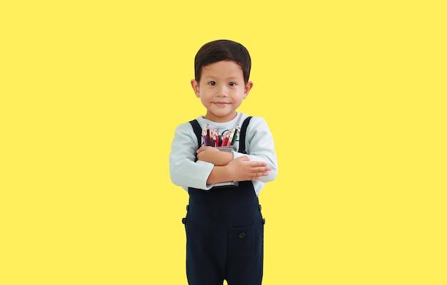 노란색 배경에 격리된 색연필 바구니를 껴안고 있는 4세 아시아 소년 초상화. 클리핑 패스가 있는 이미지