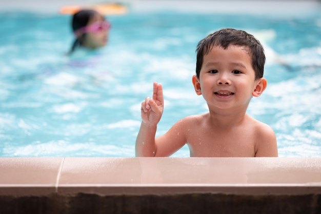 Portrait of asian little boy looking at camera and smiling while playing water in the swimming pool. summer activity and childhood lifestyle concept.