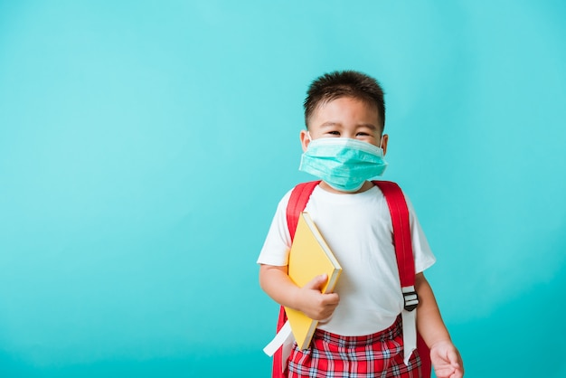 Portrait of asian little child boy kindergarten wear face mask protective and school bag hold book before going to school