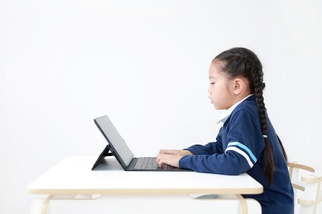 흰색 배경에 고립 된 테이블에 노트북을 사용 하 여 교복에 초상화 아시아 어린 소녀, 스튜디오 샷