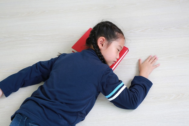 Портрет азиатской маленькой детской девочки, спящей на книге на деревянном ламинатном полу