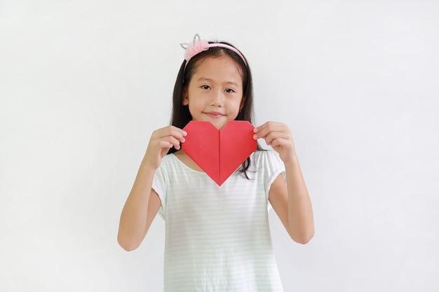 Portrait of asian little girl child holding red heart sign on white background