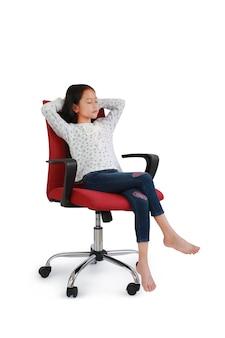 肖像画アジアの小さな女の子の子供が座って、白いスタジオの背景に分離された椅子でリラックスします。クリッピングパスを含む画像の全長