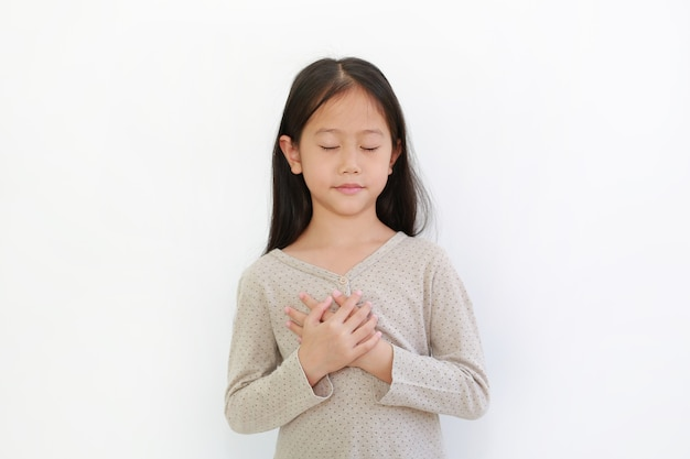 Portrait of asian little girl closed eyes and holding hands on heart gesture of love