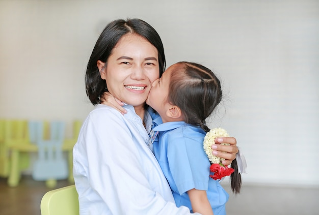 Portrait of asian little girl kissing her happy mom and hugging on mother's day in thailand. kid pay respect and give thai traditional jasmine garland to mother.