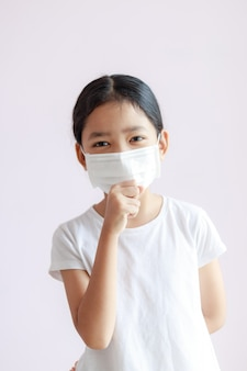 Portrait of asian little girl wears a sanitary mask and cough