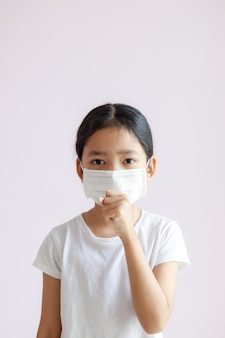 Portrait of asian little girl wears a sanitary mask and coughs