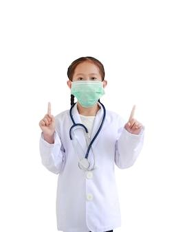 Портрет азиатской маленькой девочки в униформе врача со стетоскопом и в медицинской маске, показывающей два указательных пальца, изолированные на белом фоне.