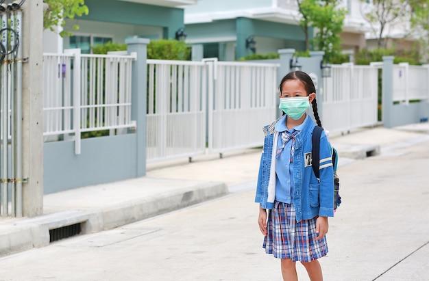 Портрет азиатской маленькой девочки в школьной форме в медицинской маске, идущей на открытом воздухе, выходит из дома, чтобы пойти в школу.