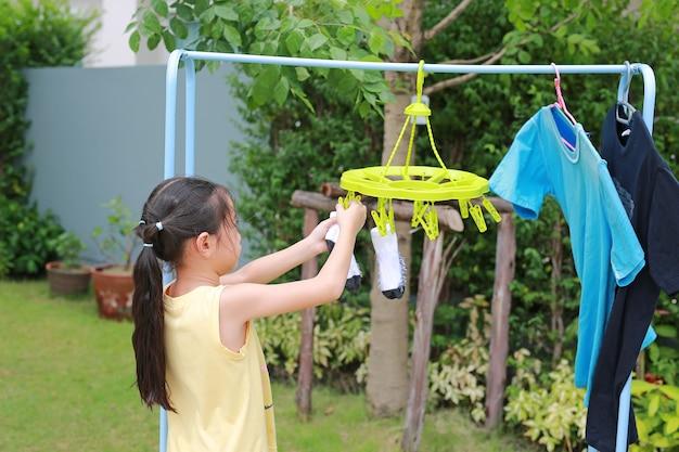 초상화 아시아 어린 소녀는 빨래집게를 걸고 양말을 걸어 옷을 말립니다. 정원에서 빨래하는 아이