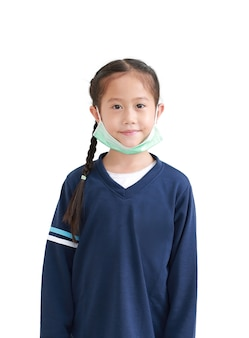 Портрет азиатской маленькой девочки ребенка в медицинской маске, перекинутой на ее подбородок, изолированном на белом фоне. на фоне концепции пандемии covid-19
