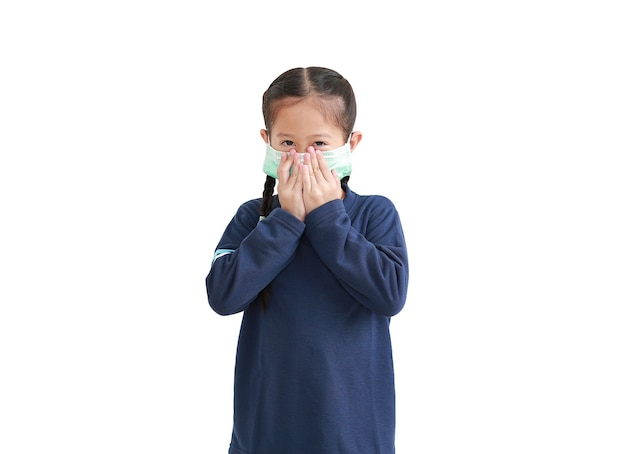 白い背景で隔離の医療マスクを身に着けている肖像画アジアの小さな子供の女の子
