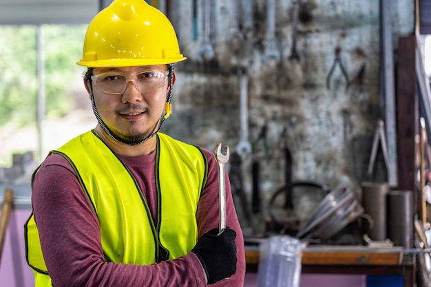 Portrait of asian machinist in safety suit holding the wrench over the stack of wrench