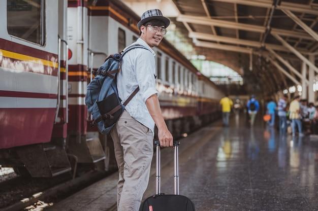 Портрет азиатского человека, несущего багаж на вокзале. концепция путешествия. туристический путешественник человек идет на вокзале.