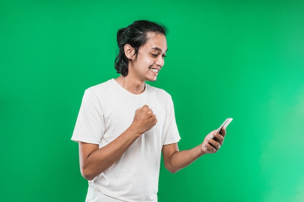 Portrait asian man holding and look handphone with happiness expression while raising one hand and making a fist, isolated on green background