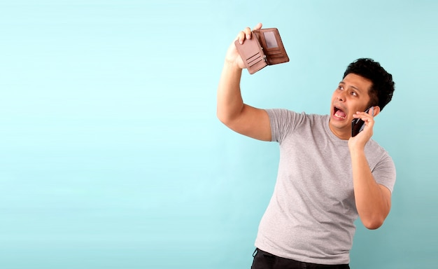 Portrait of asian man holding mobile phone a shocked, surprised speechless. holding an empty wallet on blue wall.
