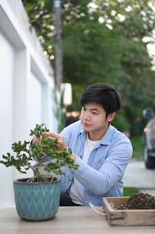Portrait of asian man is trimming bonsai plant with pruning shears at his home garden.
