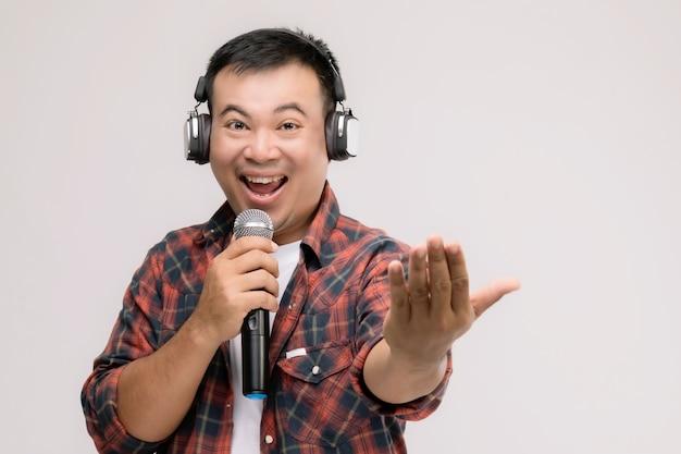 黒いヘッドフォンから歌や音楽を聞いている肖像画のアジア人男性。