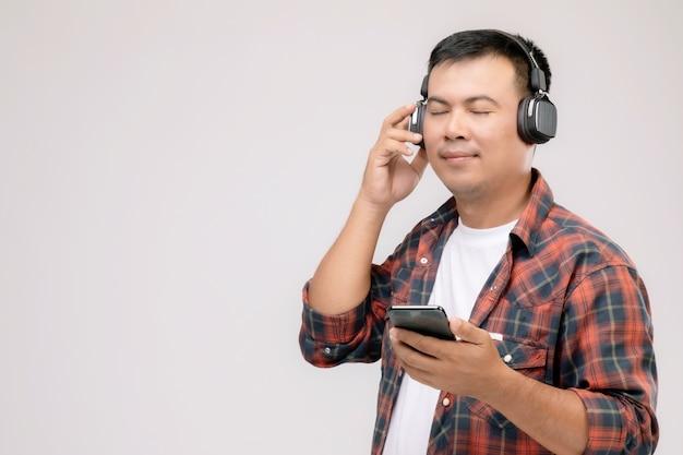 Портрет азиатского человека прослушивания песни или музыки из черных наушников.