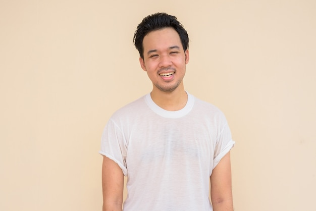 Portrait of asian man wearing casual white t-shirt against plain background outdoors