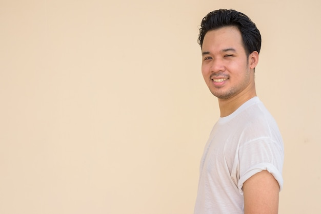 Portrait of asian man wearing white t-shirt against plain background outdoors while smiling