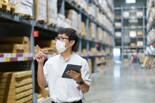 Портрет азиатские мужчины, персонал, подсчет товаров, менеджер по контролю за складом стоять, подсчет и осмотр товаров на складе