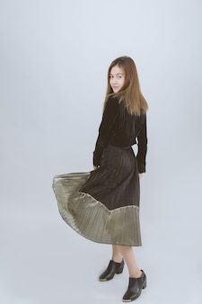 Portrait of asian model wearing long dress smiling on grey. asian female back view look at camera in studio.