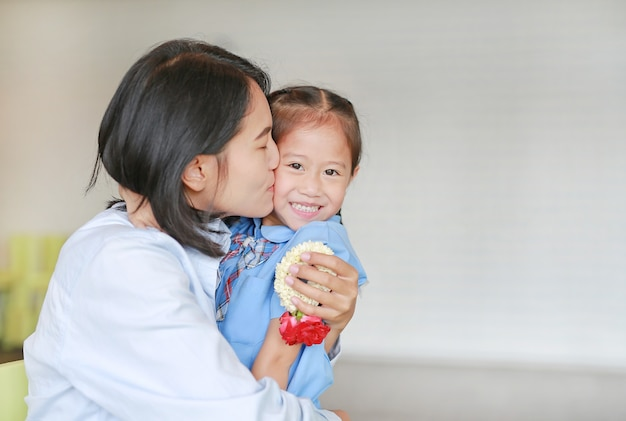 Portrait of asian mom kissing and hugging her daughter on mother's day in thailand. little child girl pay respect and give thai traditional jasmine garland to mother.