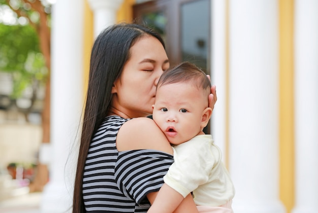 Portrait of asian mother carrying and kissing her infant baby boy outdoor.