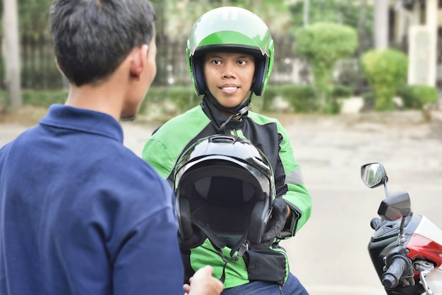 Portrait of asian motorcycle taxi driver giving the helmet