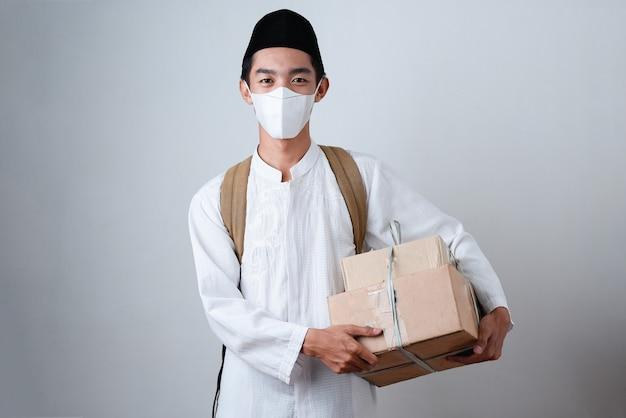 Портрет азиатского мусульманина на сером в мусульманской одежде и держащего коробку подарков с рюкзаком