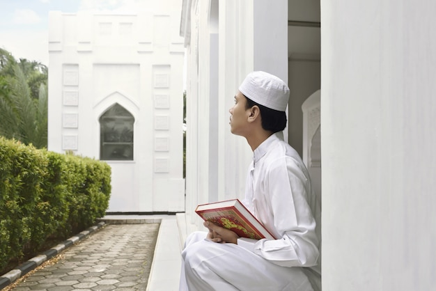 Portrait of asian muslim man holding quran