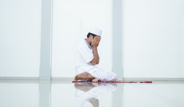 A portrait of an asian muslim man pray at mosque, the pray name is sholat, regards end of sholat