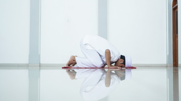 A portrait of an asian muslim man pray at mosque, the pray name is sholat, sujud movement on sholat
