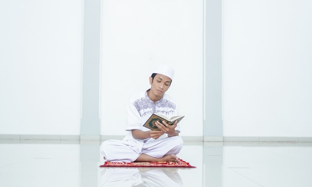 A portrait of an asian muslim man recite at mosque