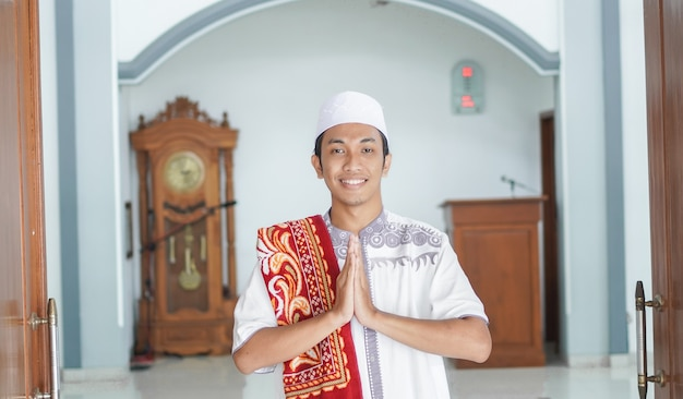 A portrait of an asian muslim man stands up in a greetting pose to namaste hands, welcoming guests, ied fitr greeting at mosque