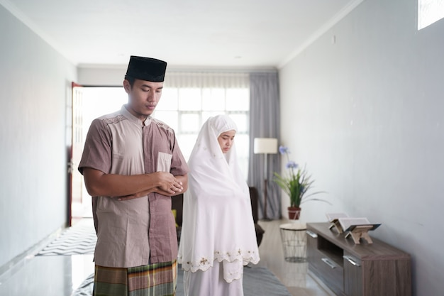 Portrait of asian muslim praying by fold arm in front of a chest at home