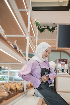 Portrait of asian muslim woman feel sick during working at the shop