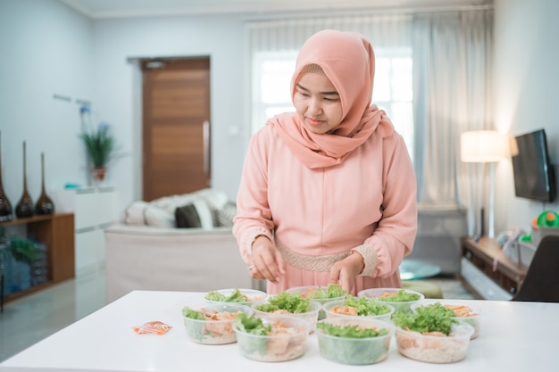 Portrait of asian muslim woman food seller preparing her product at home kitchen