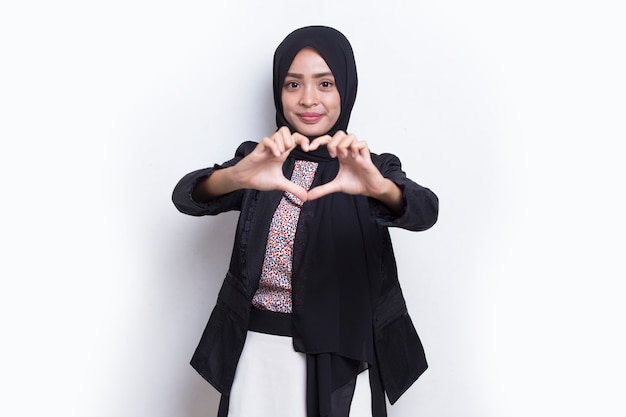 白い背景で隔離の心の愛のサインを示すヒジャーブを身に着けている肖像画アジアのイスラム教徒の女性