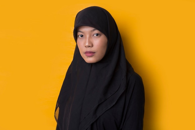Portrait of an asian muslim woman on yellow background