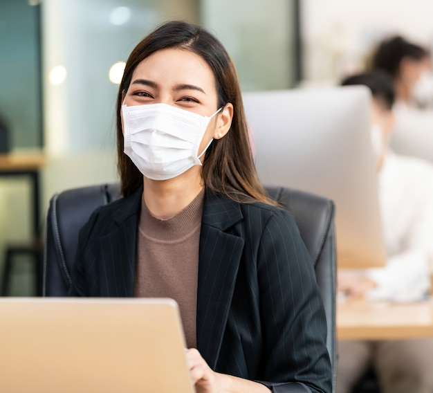 Premium Photo | Portrait of asian office employee businesswoman wear  protective face mask work in new normal office with interracial colleague  in background as social distance practice prevent coronavirus covid-19.