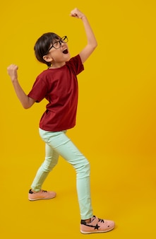 Portrait of asian pretty girl celebrating and raising hand up for successful, thai kid with glasses in red shirt have glad and joy on yellow