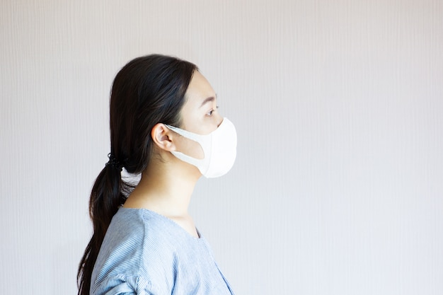 Portrait of asian pretty woman wearing a hygiene face mask close up.